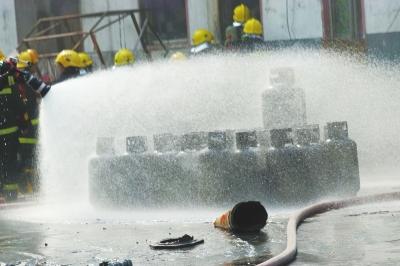 消防官兵抢出液化气罐,对其进行降温。