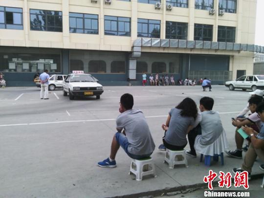 在驾校内,等待练车的90后们不忘忙里偷闲玩会儿手机。 拾冠之 摄