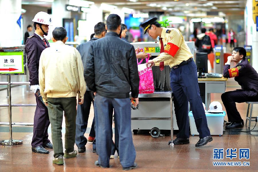北京/资料图:3月5日,广州地铁公园前站的安保人员在引导乘客将随身...