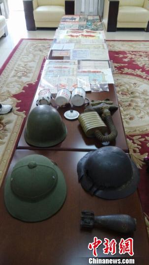 陈列桌上,摆满了张兴华捐赠的各式文物,包括《支那事变画报》、《革命军人牺牲证明书》、士兵头盔、纪念章、等共计42件战争文物。 茆振杰 摄