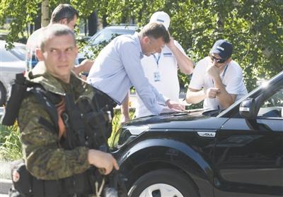 7月30日,乌克兰顿涅茨克,欧安组织调查人员看地图分析周围安全形势。由于乌内战仍在继续,调查人员已经连续4天未能进入MH17坠机现场。