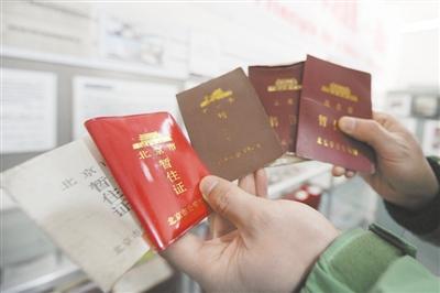 2010年3月10日,金盏乡一家打工者博物馆,负责人在整理展览的暂住证。北京将推行居住证以取代暂住证,居住证立法有望今年完成。新京报资料图片 杨杰 摄
