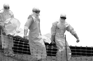 """2014年4月1日,在几内亚盖凯杜,""""无国界医生""""组织的成员身着防护服运送一名死亡患者的遗体"""