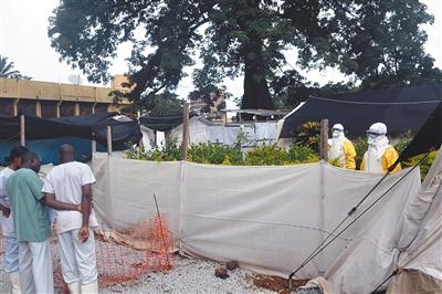 几内亚首都科纳克里一家医院,无国界医生组织的工作人员身穿防护服站在隔离区中。