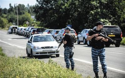 7月28日,来自澳大利亚和荷兰的调查人员前往坠机现场途中,乌克兰民间组织在其车队后面封锁道路。