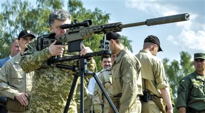7月27日,乌克兰总统波罗申科在参观国民卫队训练中心时,检查武器装备。这些武器将被送往乌东南部,与民间武装交火的前线。