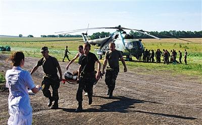 7月31日,乌克兰士兵从直升机上抬下受伤的士兵。