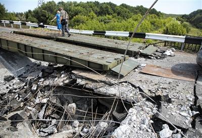 7月31日,顿涅茨克地区,民众从被炸毁的桥上走过。