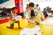 图文:跟奥运冠军学柔道 小学员整理柔道服
