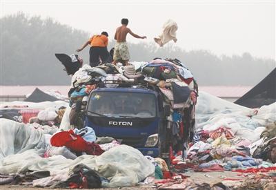 房山窦店镇的废旧衣服集散地,工人们从车上卸下大量废旧衣服和被褥。