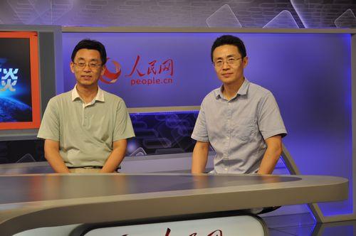 图为人民日报社高级记者白剑峰(右)