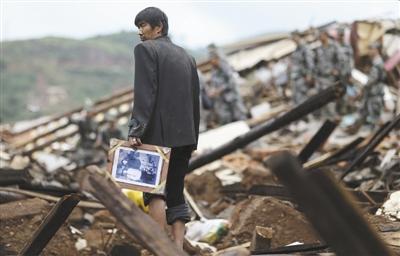 昨日,云南省�甸�h,一位中年男子左手拿著一��相框,在�U墟上站立、回首。�D/CFP
