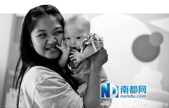 泰国代孕母亲帕特拉蒙・占播抱着生下的唐氏宝宝甘米。