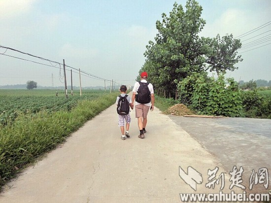 图为:走在乡间的小路上-武汉男孩牵外公徒步到岳阳 创意完成暑假作业