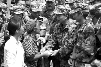 彝良武装部官兵废墟中挖出现金交给村民。新华社发