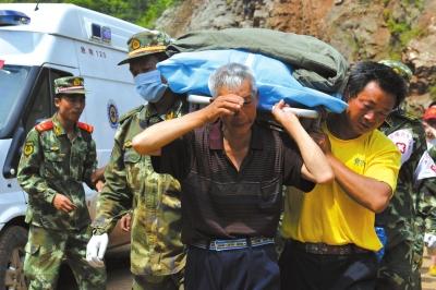救援人员和群众抬着谢樵的遗体。新华社发