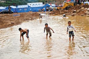 """龙头山灰街子安置点旁的水池里,几名男孩在嬉戏。看到此情此景,建筑师吴锋志说:""""今后,要让孩子们住上安心的房子。"""" 都市时报见习记者 资渔"""