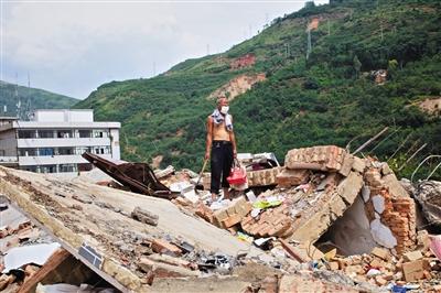 8月9日,龙头山镇,一位老者在自家房屋废墟上寻找家当。新京报记者 周岗峰 摄