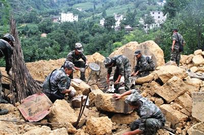地震后,部队官兵在搜救被困村民,但遇到极大困难,房屋已破碎成一米见方的土块。新华社发