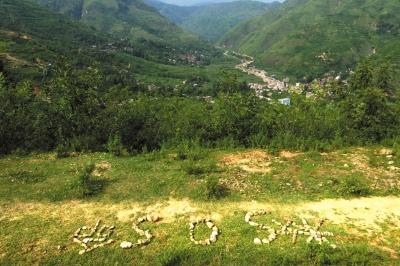 """8月6日清晨,鲁甸县龙头山镇营盘村银厂坡的山腰上,14岁男孩冯源涛用石头摆出""""救SOS命""""字样。"""