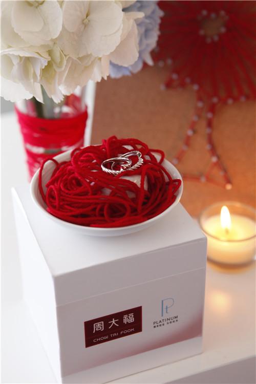 周大福铂金对戒新品在烛光的映照以及红线的衬托下散发出象征幸福的纯净光辉