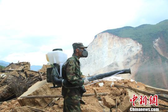 李亚涛背负便携式洗消器在废墟上洗消。 张伟 摄
