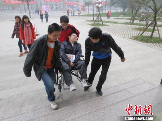 同学们抬着熊仕华上教学楼。 靳廷江 摄