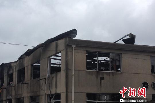 工厂发生火灾后,大火将彩钢瓦掀到围墙外 孙权 摄