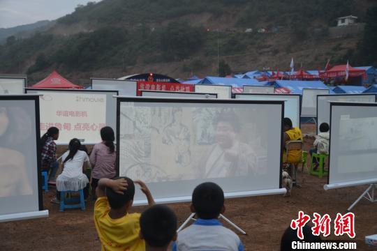 云南鲁甸灾区组织受灾群众观看大幕电影 钟欣 摄