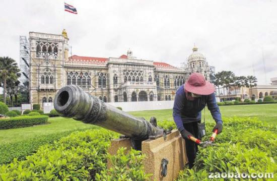 泰国总理府园地里的工人在修剪花草,背后的办公大楼也搭起了鹰架进行修葺粉刷。