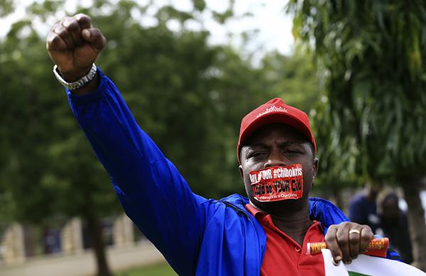 """8月12日,尼日利亚首都阿布贾,一位参加游行的青年嘴上贴着标语呼吁""""带回我们的女孩""""。"""