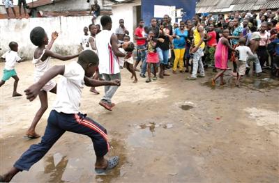 8月16日,利比里亚首都蒙罗维亚,一名男子抱着一个女孩从一个埃博拉隔离区中跑出。