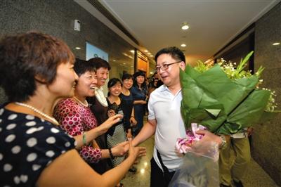 8月15日,传染病专家李鑫(右一)和送行的亲友同事告别。