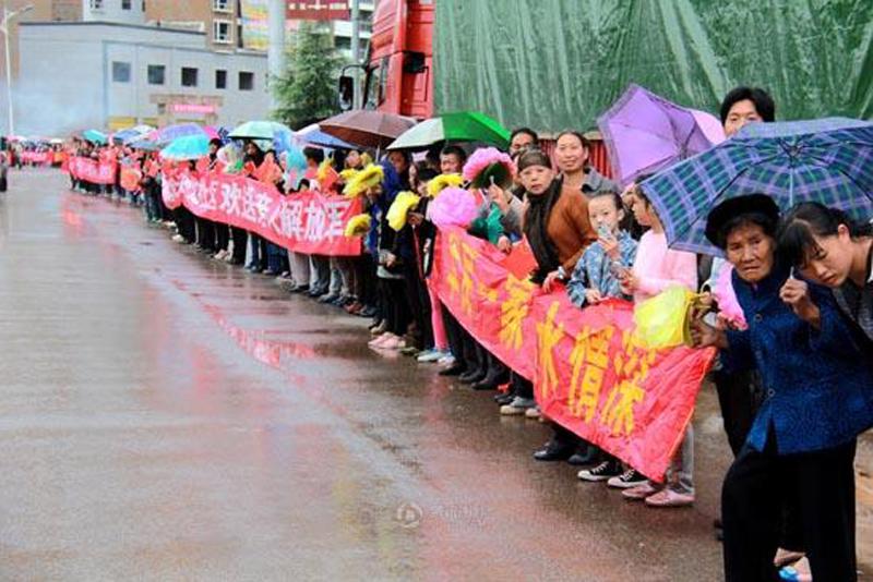 """地震无情人有情,参加鲁甸抗震救灾的解放军踏上归程之际,震区的姑娘们打出横幅,表示""""嫁人要嫁解放军!""""。"""