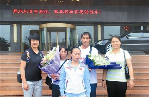 蒋惠花与教练邓惠洁(左)、启蒙教练徐维妹(右)及父母在一起。