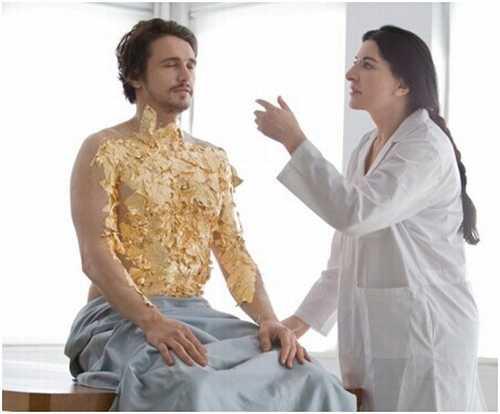 詹姆斯安静地坐在那里,裸着上身,马丽娜为他贴满了金树叶,将他塑造成一座金色的活雕像。