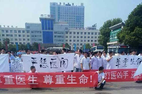 8月21日上午,岳阳市二人民医院两百多名医务人员在该院门诊楼前静坐,抗议前一天发生在该院的暴力伤医事件。 微博图片