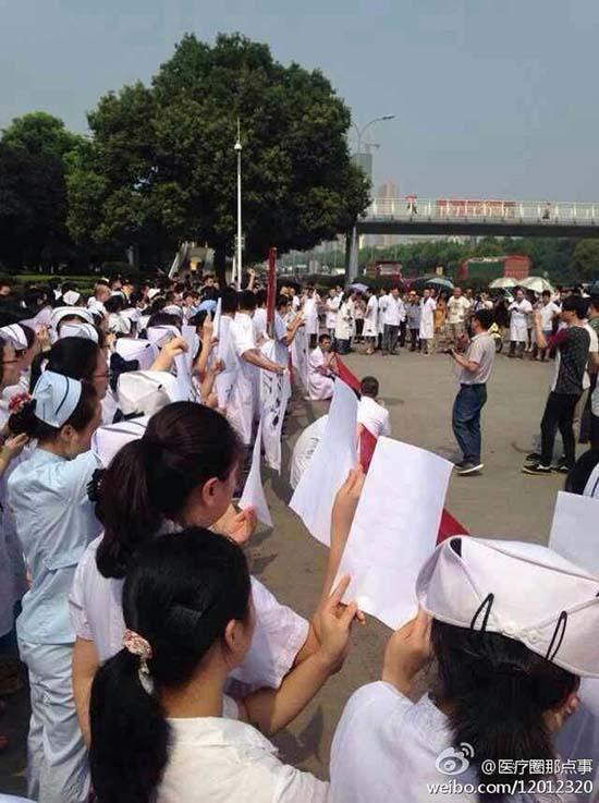 8月21日上午,岳阳市二人民医院两百多名医务人员在该院门诊楼前静坐抗议。 微博图片