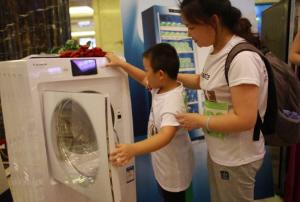 小朋友饶有兴趣地体验卡萨帝云裳系列洗衣机。
