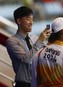 图文:刘翔观看青奥跨栏比赛 刘翔拿手机拍照