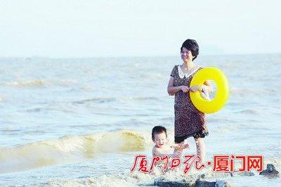 孩子在大人陪同下玩水。