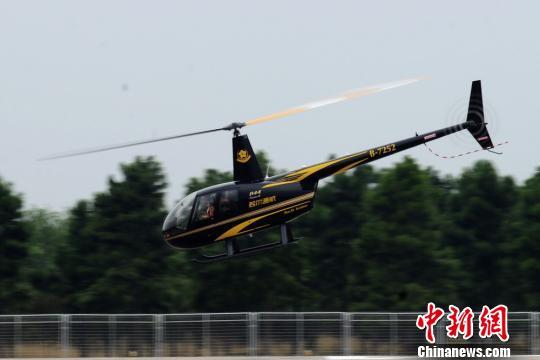 图为直升机在机场降落后,工作人员护送试乘人员。 王思哲 摄