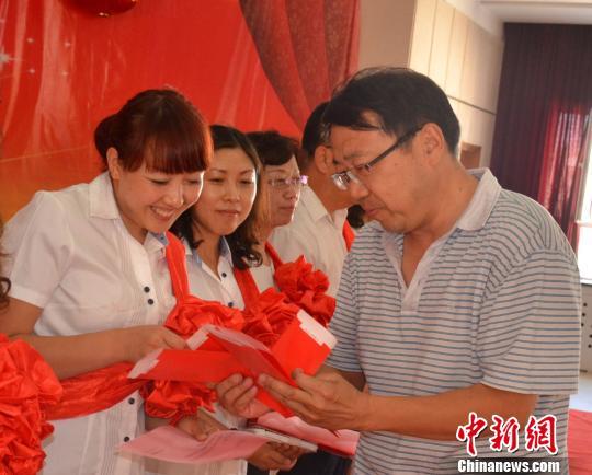 图为美术教师崔逢春为学校的11位教师发红包。 魏宝山 摄