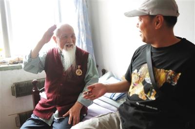 """昨日,""""寻找抗战老兵""""志愿者薛刚,向93岁国民党老兵陈模群颁发一枚民间制作的抗战纪念徽章,老人回礼致谢。新京报记者 秦斌 摄"""