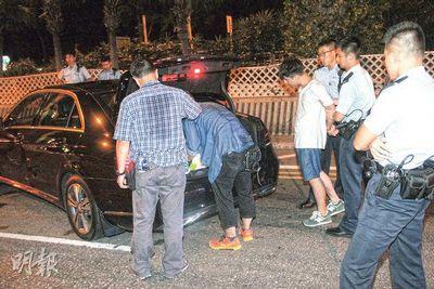 驾驶奔驰的青年(穿短裤者)撞车后殴打的士司机及便衣警长,事后被多名警员反锁双手制服,疑因醉酒而步履不稳。来源 香港《明报》