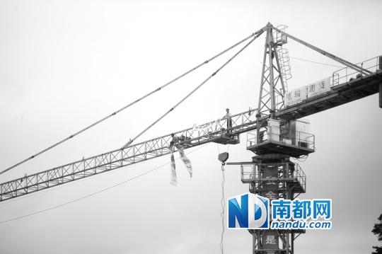 两男子爬上塔吊在风雨中僵持着。南都记者 田飞 摄