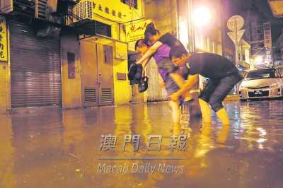 男子背起女士涉水过路。来源:《澳门日报》