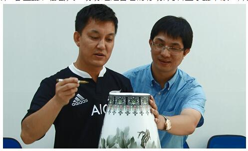 """李锐(左)将收藏多年的瓷艺堂""""花开盛世""""五彩福瓶参与物物交换并签名"""