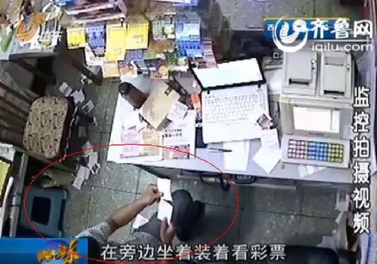 监控显示,这名男子拿起一本彩票装进裤兜,然后假装看彩票,努力掩饰自己的盗窃行为。(视频截图)