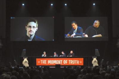"""15日,新西兰奥克兰,新西兰网络大亨多特康姆(右)与曝光""""棱镜门""""的记者格林伍德(中)视频连线斯诺登(左)。图/CFP"""